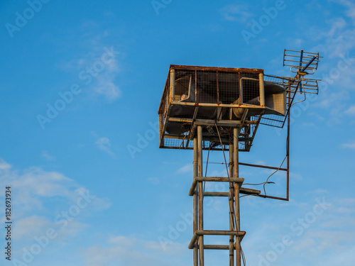 Old public loudspeakers broadcast vintage style on high tower the blue sky background