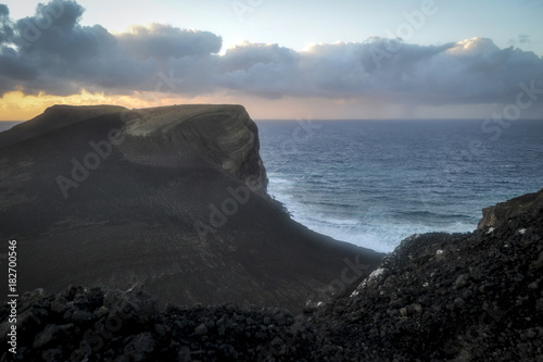 Foto op Canvas Zee zonsondergang a cliff of lava illuminated by the setting sun on the island of the Azores