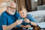 Pleasurable entertainment. Happy cheerful elderly man sitting with his grandson and holding a puzzle piece while collecting them together with him - 182703945