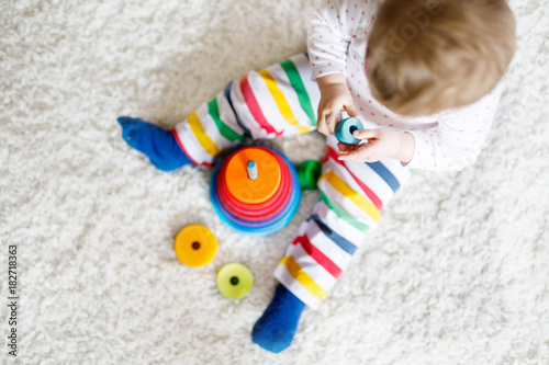 Adorable cute beautiful little baby girl playing with educational colorful wooden rainboy toy pyramid