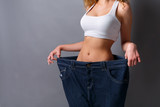 Woman wearing jeans much bigger size - 182723990