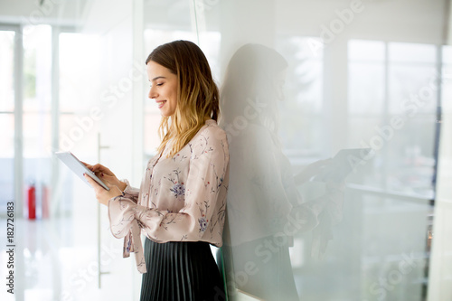 Wall mural Young businesswoman with tablet in office