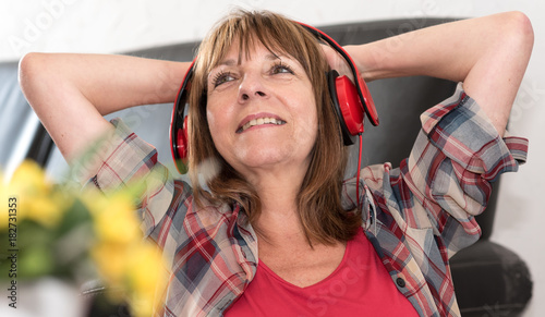 Plexiglas Muziek Happy mature woman listening to music