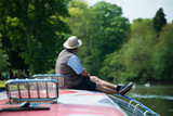 man sat on front of boat with union jack pattern - 182735127