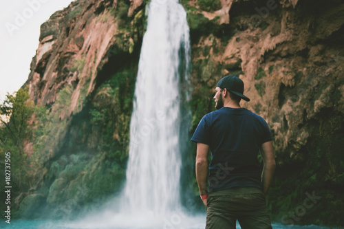 Man in front of beautiful blue waterfall