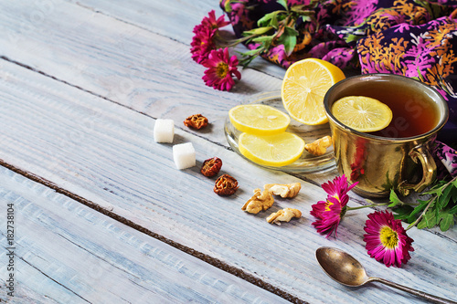 Poster Cup of tea, lemon and flowers on a white wooden table