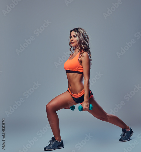 Plexiglas Fitness Sporty female over grey background.