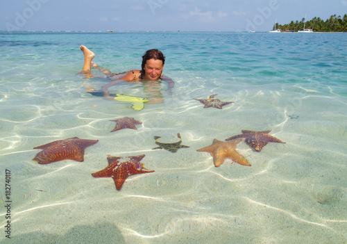 Leinwanddruck Bild Mädchen im Flachen Wasser einer Lagune, umgeben von Seesternen