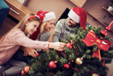Mom, dad and daughter decorating Christmas tree. - 182740507