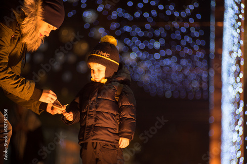 Fotobehang Boeddha Mother is igniting sparkler in her son's hand Family is celebrating New Year on a street. There are many defocused Christmas lights on blurred background.