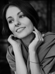 Black and white vertical portrait of young beautiful woman indoor. Caucasian girl with calm smile.