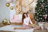 The smiling young woman unpacks a Christmas gift. The girl sits in beautifully decorated room with a pink sofa and a golden interior near the fir-tree decorated with toys, spheres and garlands.