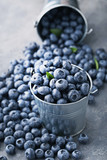 Ripe blueberries in buckets on grey wooden table - 182759528