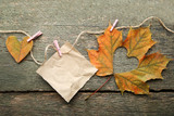 Dry maple leaf with heart and sheet of paper on grey wooden table - 182759554