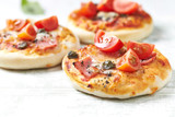 Home baked mini pizza topped with ham, cherry tomatoes and capers on wooden background - 182762726