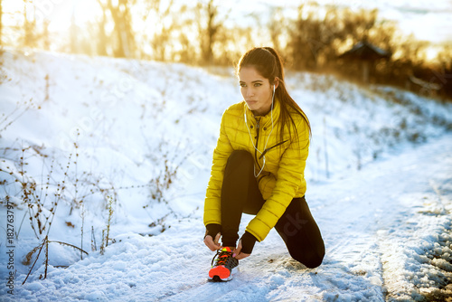 Młoda sportive zdrowa skupiająca się dziewczyna wiąże shoelaces w zimy sportswear na śnieżnej zimy drodze z słuchawkami w pogodnym ranku.
