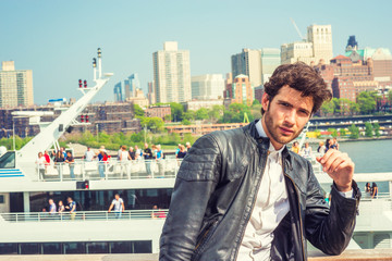 European businessman traveling on East River in New York. Wearing black leather jacket, young guy with beard, standing on deck, waiting for cruse, enjoying sunny, warm weather in spring day. Vacation