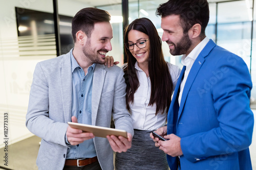 Businesspeople using digital tablet in office together