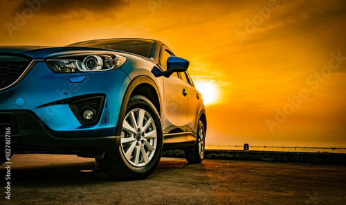 Leinwandbild Motiv Blue compact SUV car with sport and modern design parked on concrete road by the sea at sunset. Environmentally friendly technology. Business success concept.
