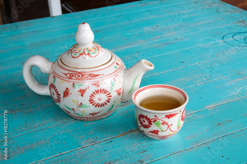 Papiers peints The Hot tea in a teapot and a cup on blue wooden table.