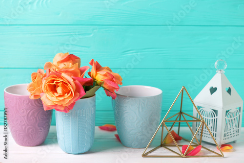 Bunch of fresh orange roses  against  turquoise  wall. Place for text. Floral still life.