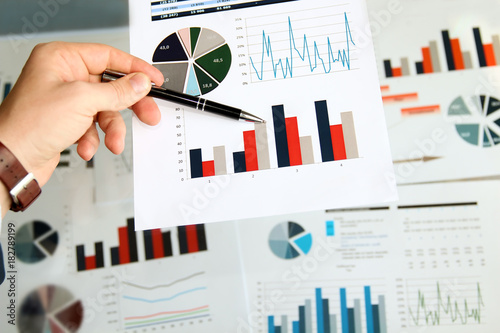 Wall mural Business man working and analyzing financial figures on a graphs