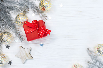 red gift box and silver christmas fir tree branches decorated with glowing garland on white wooden background with star confetti