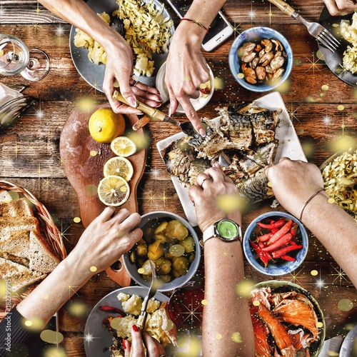 Christmas dinner. Falling golden snowflakes. Cheers Top of view of a nicely served wooden table Christmas dinner with tasty dishes and snacks, friends are toasting with glasses of red and white wine - 182799915