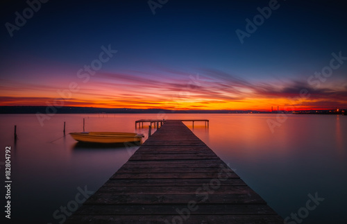 Drewniany dok i łódź rybacka przy jeziorem, zmierzchu strzał