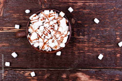 Papiers peints Chocolat Hot chocolate with marshmallow in brown cup on wooden background. Copy space.