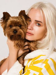 young beautiful blonde woman standing on white background with little dog yorkshire terrier