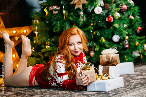 Beautiful sexy girl in red underwear and sweater lying near Christmas tree and o Plakát
