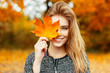 Leinwanddruck Bild - Beautiful happy woman with a smile holds an autumn yellow leaf near the face