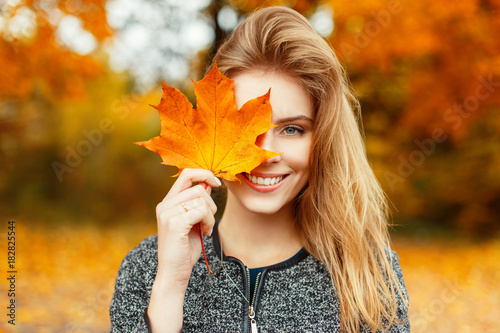 Leinwanddruck Bild Beautiful happy woman with a smile holds an autumn yellow leaf near the face