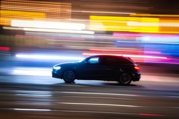 Automobile che sfreccia veloce di notte per le vie con luci colorate di una  grande città