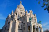 Sacré Coeur cathedral white facade front with deep blue sky above, Paris, France