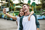 Young couple having fun together at an amusement park - 182830725