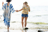 Girlfriends holding hands and walking on the beach - 182831965