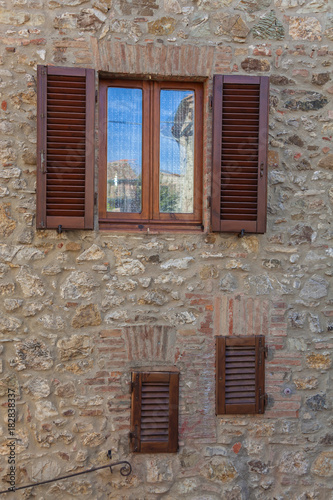 Fototapeta Reflection of street in a window with shutters in the midst of shabby old wall