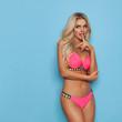Seductive Sexy Blond Woman In Pink Bikini Is Looking Away