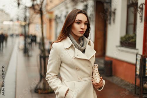 Poster Stylish young woman in trendy autumn coat with handbag walking outdoors in the c