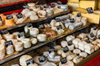 Different cheeses on the counter of a small store at the Aligre Market. Paris, France