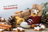 Kinderschuh mit Süßigkeiten, Geschenken und Weihnachtskugeln auf rustikalem Holz, Text  Am 6. Dezember ist Nikolaustag - 182853137