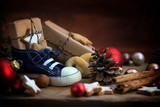 Children's shoe with sweets and gifts for St. Nicholas Day on December 6th at Christmas time on rustic wood, traditional custom in Germany called Nikolaus - 182854571