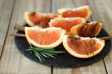 Orange with cinnamon powder and rosemary served on black slate board on wooden table. Portion of sliced orange fruit. Healthy dessert