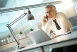 Businessman in office talking on smartphone - 182861901
