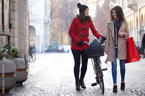 Wall mural young women walking after shopping