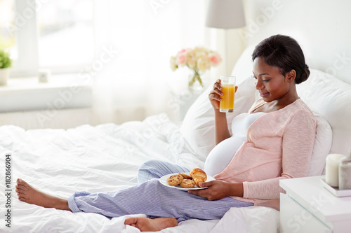 Foto op Canvas Sap pregnant woman with orange juice and pastry in bed