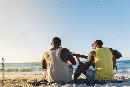 Two cuban friends having fun in the beach with his guitar.
