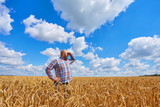 Farmer walking through a wheat field - 182875966